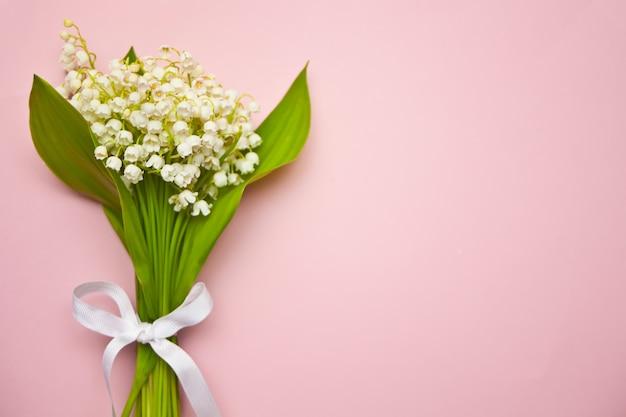Maiglöckchen blüht auf rosa hintergrund