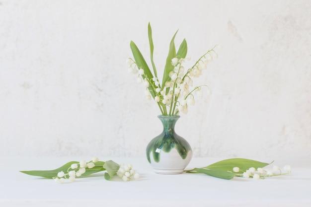 Maiglöckchen in der kleinen vase auf der alten weißen wand des hintergrunds