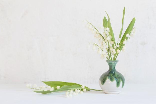 Maiglöckchen in kleiner vase auf oberflächlicher alter weißer wand
