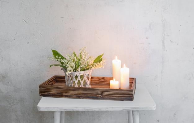 Maiglöckchen in vase mit brennenden kerzen auf der oberfläche alte weiße wand