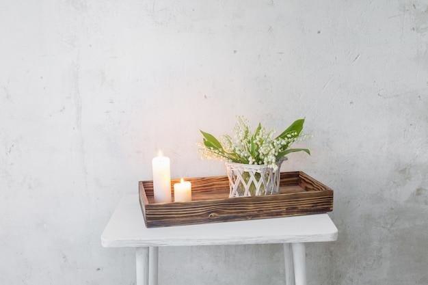 Maiglöckchen in vase mit brennenden kerzen auf hintergrund alte weiße wand