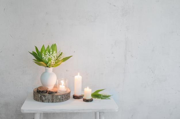 Maiglöckchen in vase mit kerzen auf oberfläche alte weiße wand