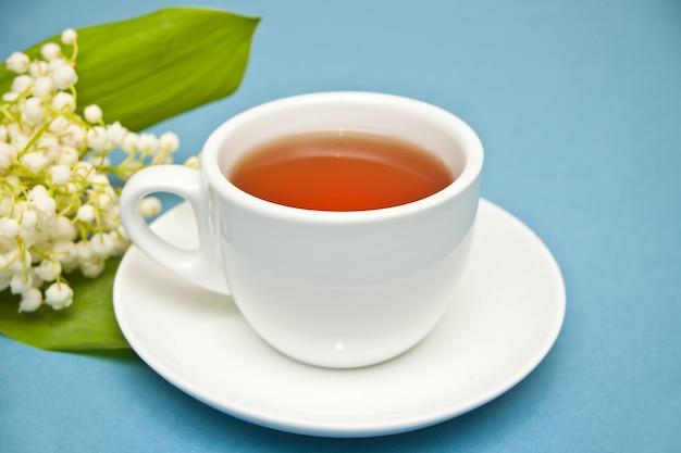 Maiglöckchenblumen und tasse tee auf blauem hintergrund. flache lage, draufsicht, kopierraum.