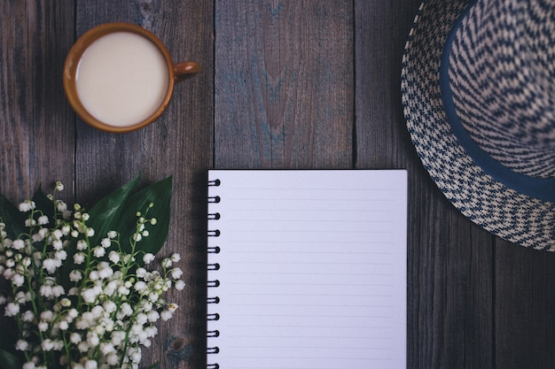 Maiglöckchenblumenstrauß, ein notizbuch, hut, tasse tee mith milch, auf holztisch