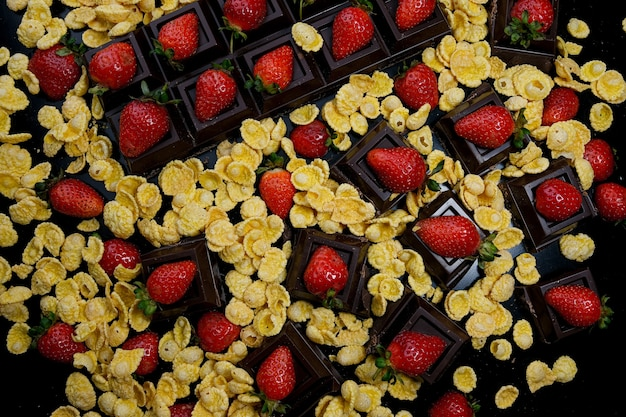 Mais-erdbeer-dessert in schokolade vor dunklem hintergrund