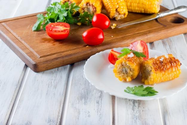 Mais gegrillt mit tomaten und grüns auf einer platte