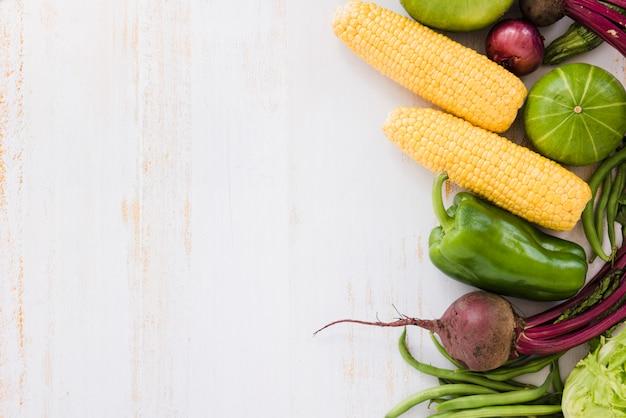 Mais; grüne paprika; rote beete; zwiebel; paprika und kürbis auf weißem schreibtisch aus holz