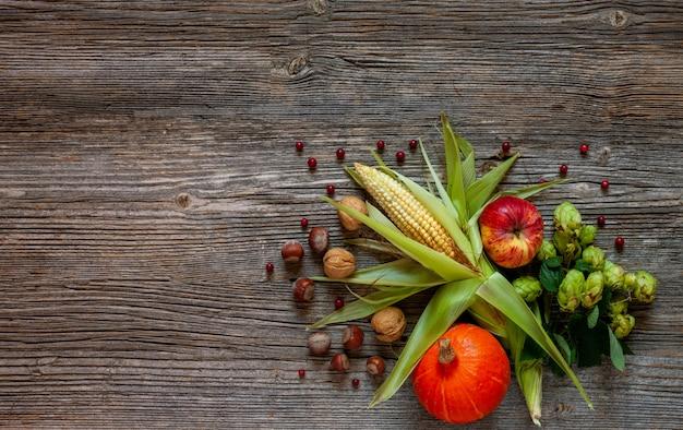Mais, kürbis, äpfel, hopfen und nüsse auf einem hölzernen hintergrund der weinlese.