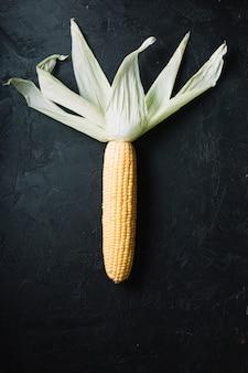 Mais mit blättern auf einer draufsicht des schwarzen schmutzhintergrundes