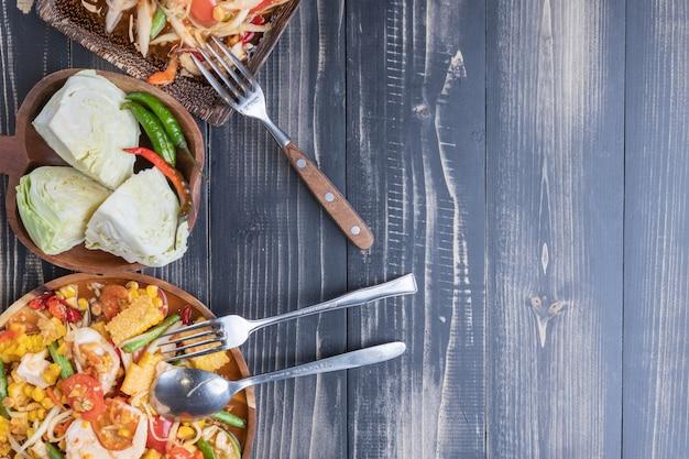 Mais und papayasalat auf thailändischer art der hölzernen platte