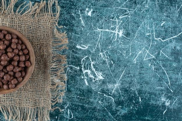 Maisbällchen in einer schüssel auf einem handtuch auf dem blauen tisch.