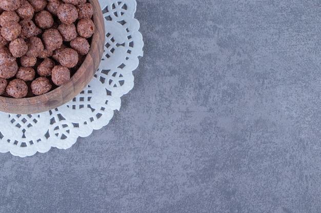 Maisbällchen in einer schüssel auf einem untersetzer auf dem marmorhintergrund.