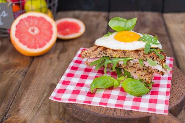 Maisbrot mit eischinken zum frühstück. ein gesundes und leckeres frühstück. hölzern . fitness essen, toast.