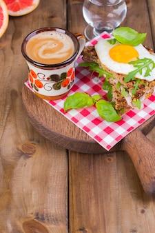 Maisbrot mit eischinken zum frühstück. ein gesundes und leckeres frühstück und kaffee. hölzern . fitness essen, toast.