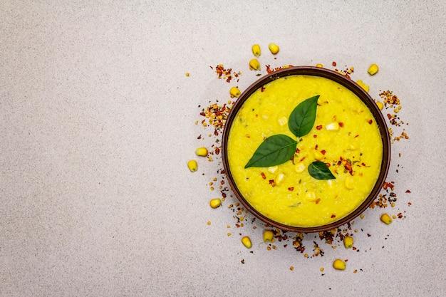 Maiscremesuppe mit frischem gemüse, kräutern und gewürzen.