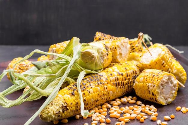 Maiskörner gegrillter mais mit blättern. platz kopieren. rostiger und schwarzer hintergrund.
