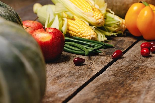 Maiskolben, äpfel und pfeffer auf holztisch