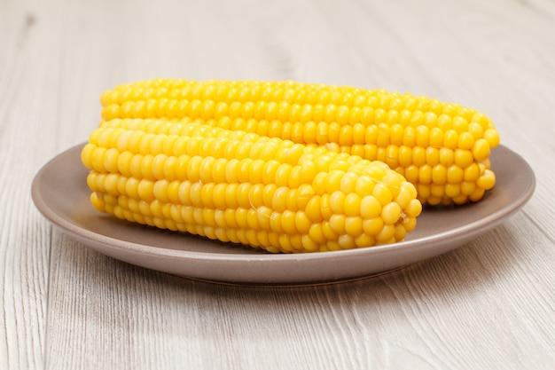 Maiskolben gekochter mais auf porzellanteller mit grauem holzhintergrund.