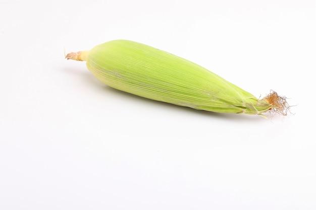 Maiskolben mit grünen blättern isoliert auf weißer oberfläche.