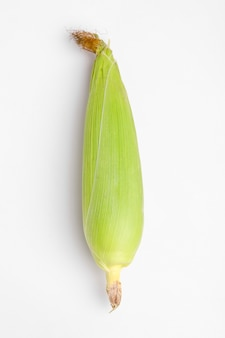Maiskolben mit grünen blättern lokalisiert auf weißem hintergrund.