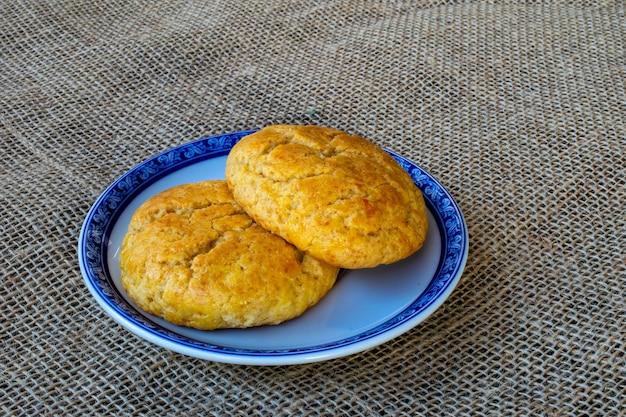 Maiskuchen auf teller mit blauem rand auf jute-tischdecke. broa de milho - typisch brasilianischer keks