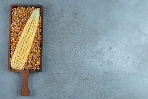 Maispflanze auf braunen bohnen auf einer holzplatte. foto in hoher qualität