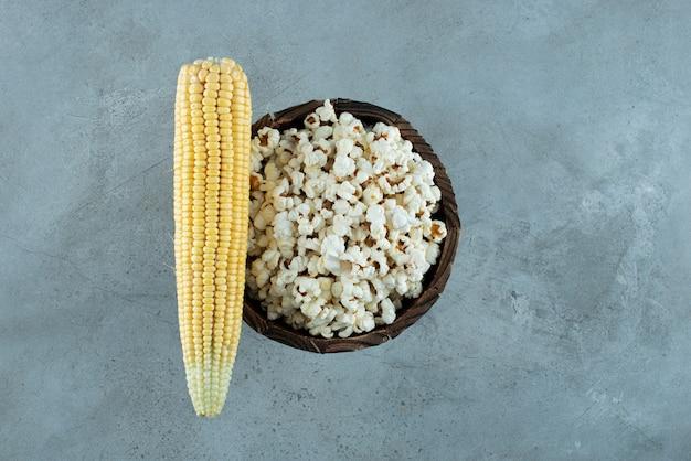 Maispflanzensamen und popcorn auf blauem hintergrund. foto in hoher qualität