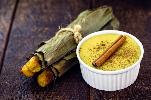 Maisquark, grüner maisbrei, mit maisbrot, süßigkeiten, die typisch für die ländlichen feste im juni in brasilien sind
