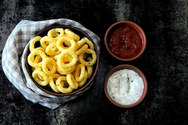 Maisringe in einer schüssel mit roter und weißer sauce. flache lage.