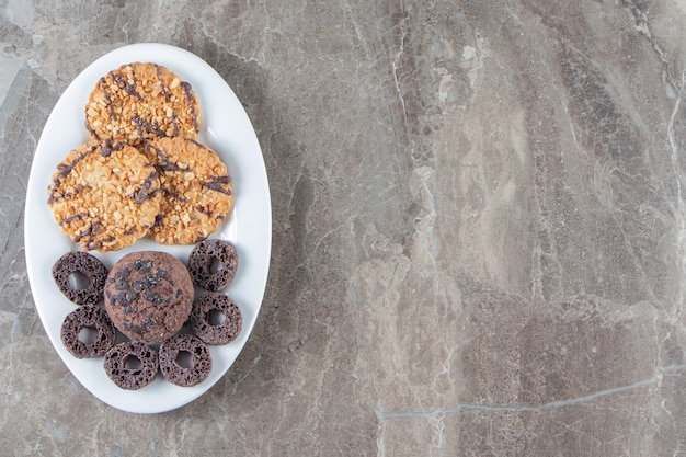 Maisringe und hausgemachte kekse auf einem teller auf marmor.