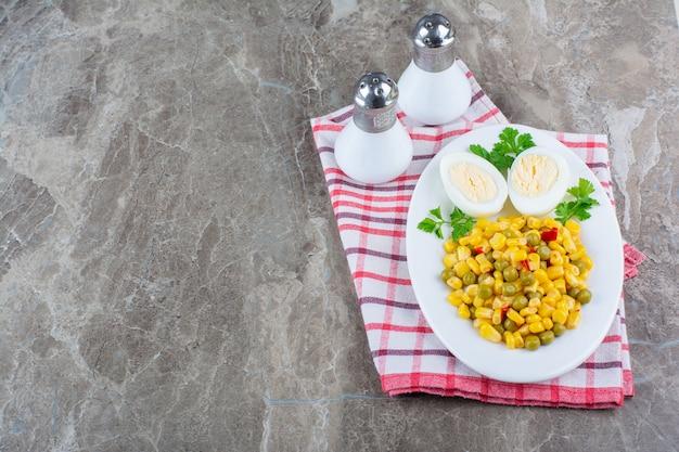 Maissalat und geschnittenes ei auf einem teller neben salz auf geschirrtuch, auf dem marmor.