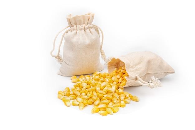 Maissamen in einem leinensack auf weißem hintergrund.