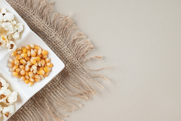 Maissamen mit popcorns in einer weißen platte.