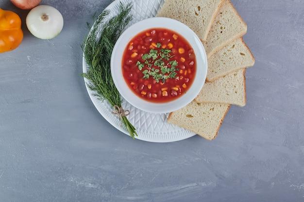Maissuppe in tomatensauce mit einem bund dill.