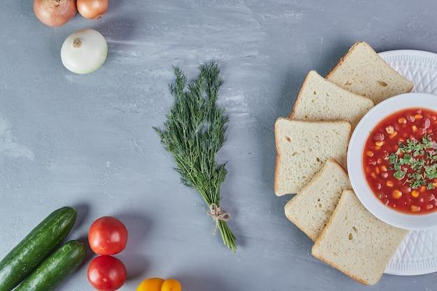 Maissuppe in tomatensauce mit zwiebeln und kräutern.