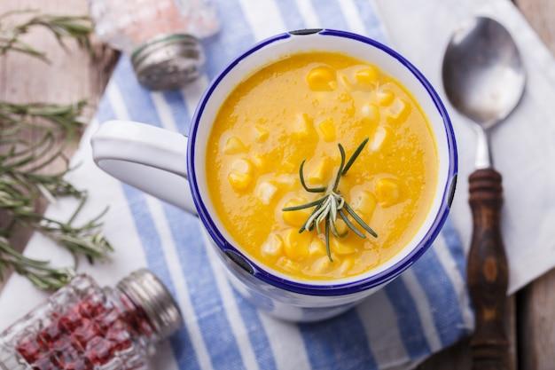 Maissuppe mit currypaste und rosmarin, in einer tasse.