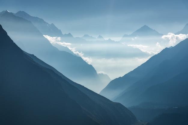 Majestätische ansicht der schattenbilder der berge und der niedrigen wolken bei sonnenuntergang in nepal