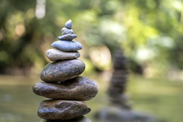 Majestätische aufnahme einer steinpyramide, die auf einem flusswasser balanciert ist