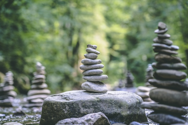 Majestätische aufnahme vieler steinpyramiden, die auf einem flusswasser balanciert sind