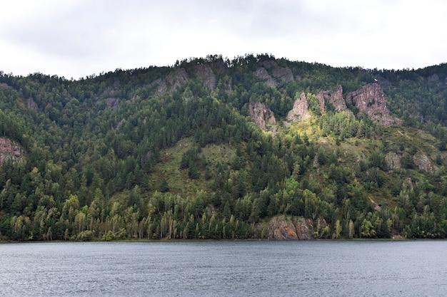 Majestätische berge und bewaldete felsen am ufer des flusses bereisen sie die schönheit der natur