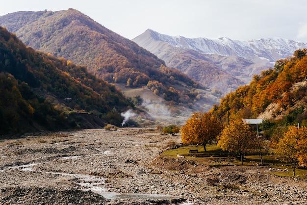 Majestätische bezaubernde natur, die berghänge sind mit pflanzen und bäumen bedeckt, rauch vom feuer