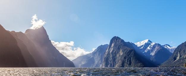 Majestätische schneebedeckte gipfel des milford sound mit sonnenstrahlen. fiordland, neuseeland