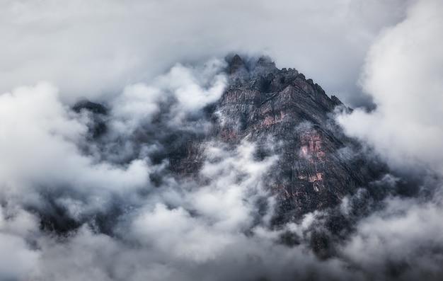 Majestätische szene mit bergen in wolken am bewölkten abend