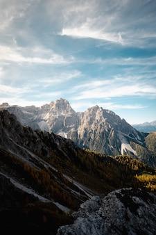Majestätische wolkenlandschaft über felsigem gras bedeckten dolomiten in italien mit schneeflecken