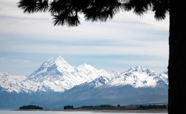 Majestätischer bergkoch mit schnee bedeckt, umrahmt von baumsilhouette mt cook neuseeland
