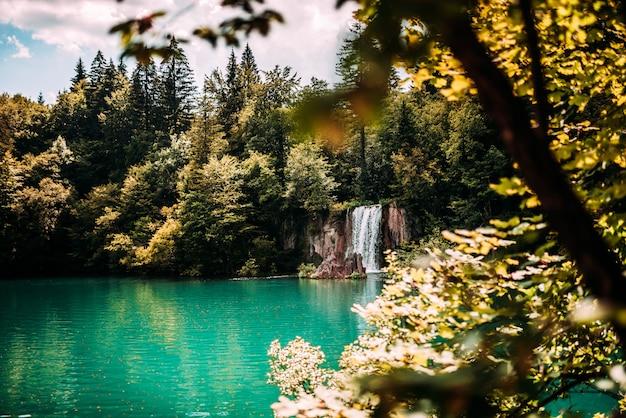 Majestätischer gebirgswasserfall und türkisfarbenes seewasser.
