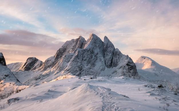 Majestätischer gebirgszug mit schneefällen am sonnenaufgangmorgen