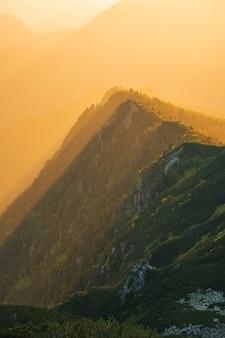 Majestätischer goldener sonnenuntergang mit sonnigen strahlen in der großen berglandschaft. nationalpark der hohen tatra, polen