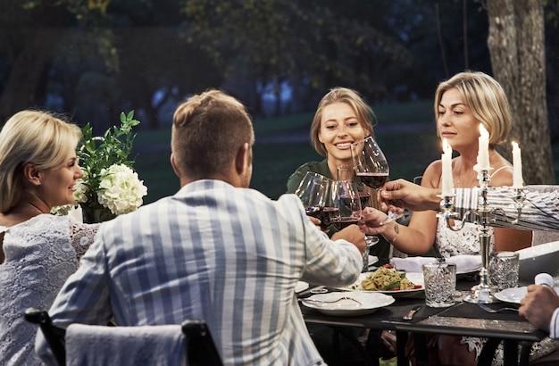 Majestätischer moment. eine gruppe erwachsener freunde ruht sich abends im hinterhof des restaurants aus und unterhält sich.
