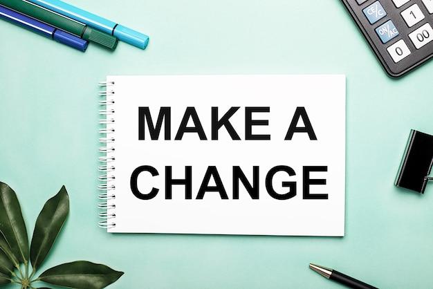 Make a change steht auf einem weißen blatt auf einer blauen fläche in der nähe des briefpapiers und des scheffler-blattes. aufruf zum handeln. motivationskonzept